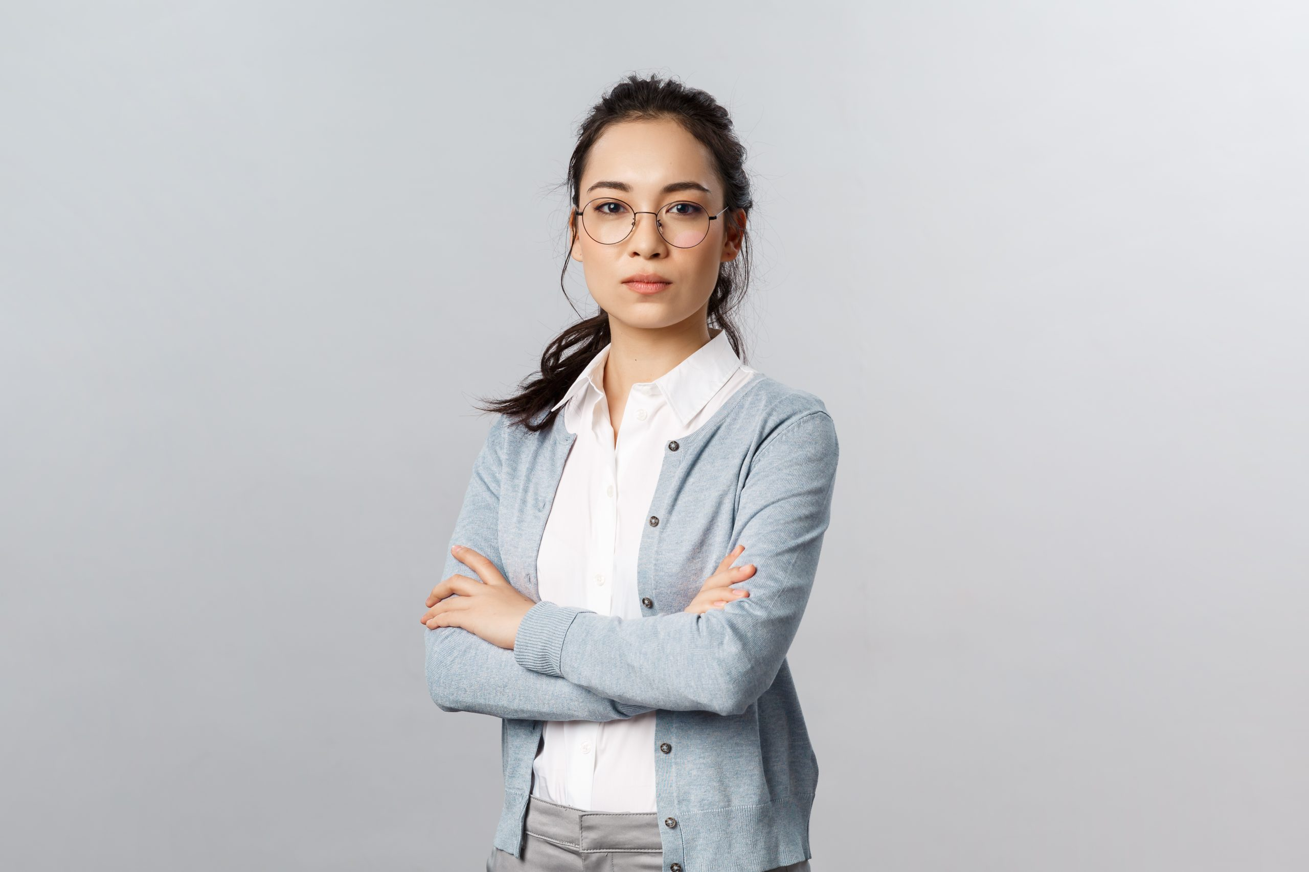 Serious-looking determined attractive asian woman, tutor or teacher starting online lesson with class standing self-assured with normal focused expression, cross arms on chest.